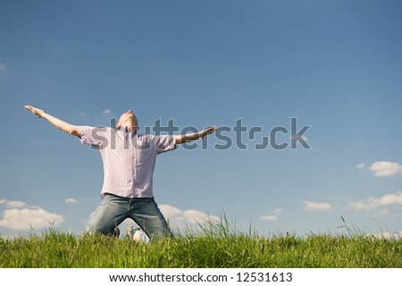 Happy young man is raising his arms into the sky