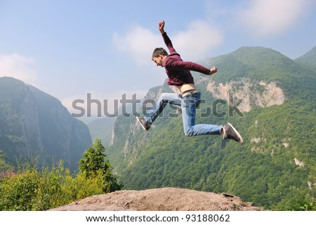 happy young man jump in nature while representing healthy lifestyle freedom and active concept - stock photo