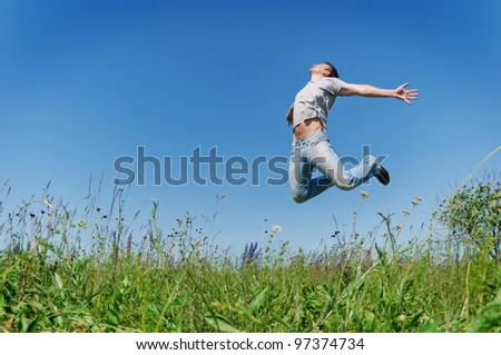 Happy young man jump on field - stock photo
