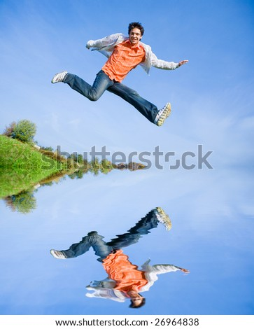 Happy young man - jumping  against the backdrop of blue sky. - stock photo