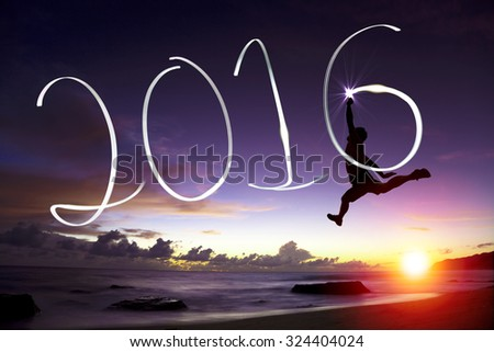 happy young man jumping  and drawing 2016 in the air - stock photo