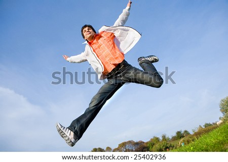 Happy young man - jumping  end fly in blue sky.