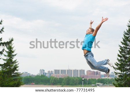 Happy young man jumping in air with arms extended - stock photo