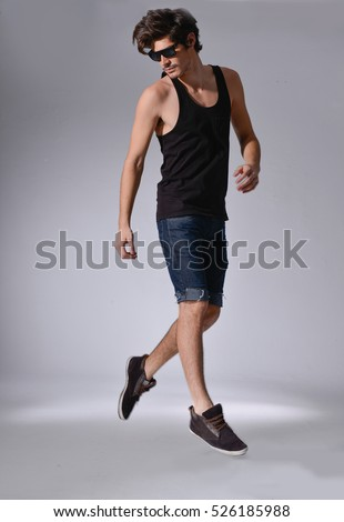 Happy young man jumping in joy, isolated on light background