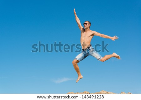 happy young man jumping on a background of blue sky, spreading his hands