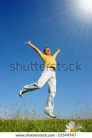 Happy young man jumping on the meadow, summer sunny day - stock photo