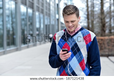 Happy young man listening to music on his mobile phone - stock photo
