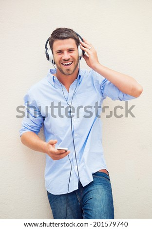 Happy young man listening to music with headphones  - stock photo