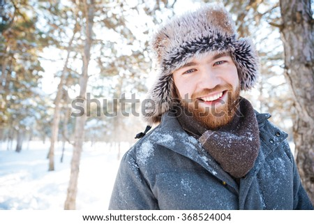 Happy young man looking at camera in winter ark - stock photo