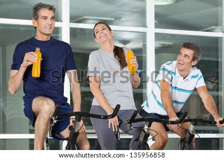 Happy young man looking at friends holding juice bottles while exercising on spinning bike in health club - stock photo