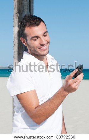 Happy young man looking at news and messaging on his smart phone at beach - stock photo