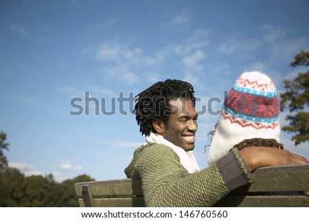 Happy young man looking at woman while sitting on park bench