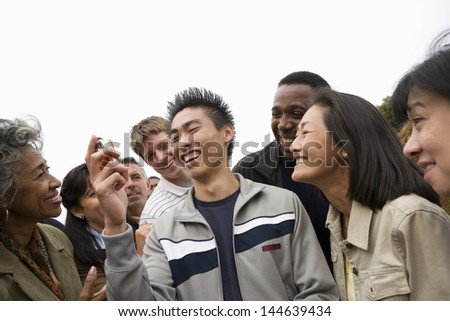 Happy young man looking holding mobile phone with people in the background - stock photo