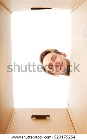 Happy young man looking inside box
