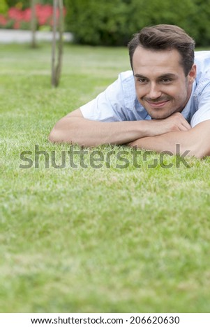 Happy young man lying on grass in park - stock photo