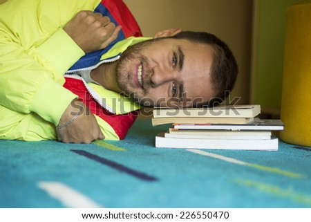 Happy young man lying on the floor on books