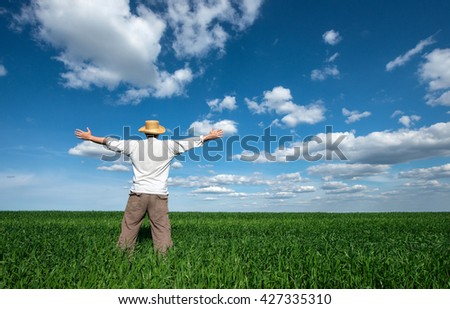 happy young man on green field of wheat