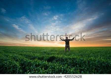 happy young man on green field of wheat at sunrise