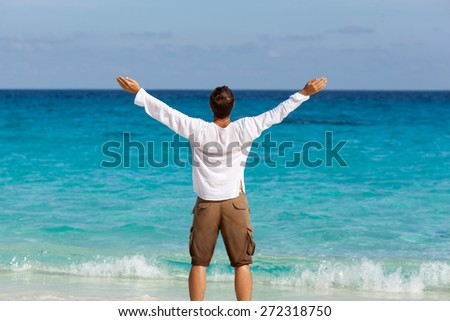 happy young man on the tropical white sand beach rising up hands - stock photo