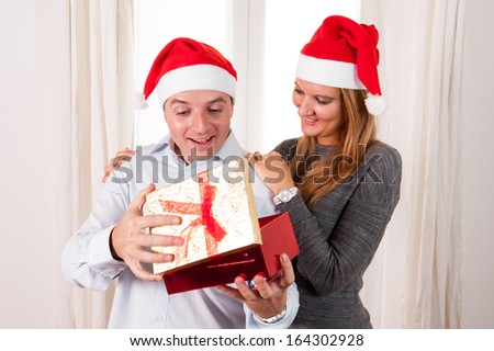 Happy Young Man Opening Christmas Present with beautiful woman