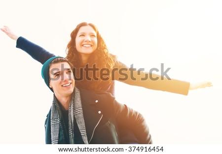 Happy young man piggybacking his girlfriend - stock photo