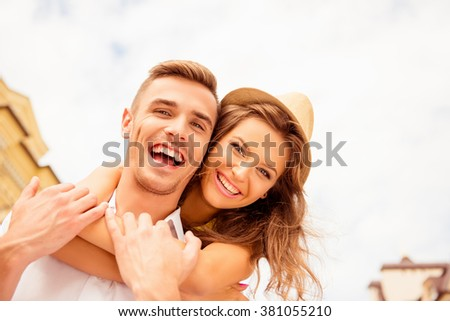 Happy young man piggybacking his girlfriend on street - stock photo