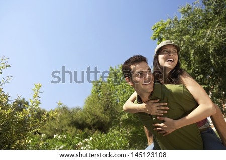 Happy young man piggybacking woman at park - stock photo