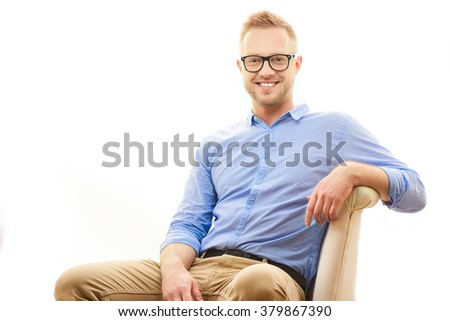 Happy young man. Portrait of handsome young man in casual blue shirt and dioptrical glasses sitting in comfortable pose isolated on white background - stock photo