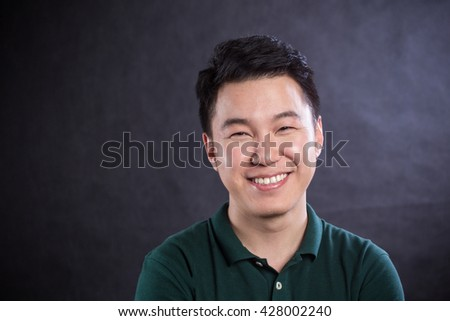 Happy young man. Portrait of handsome young man in casual shirt keeping arms crossed and smiling while standing against grey background - stock photo