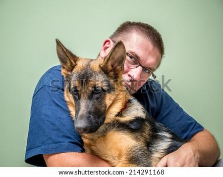 Happy young man posing with its German shepherd pet - stock photo