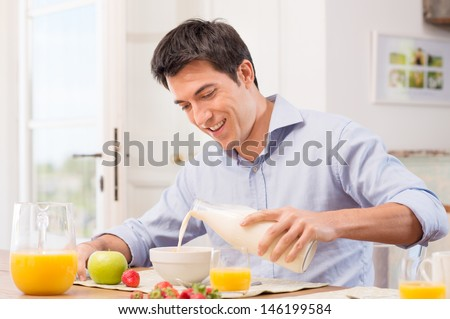 Happy Young Man Pouring Milk Into Bowl For Breakfast - stock photo