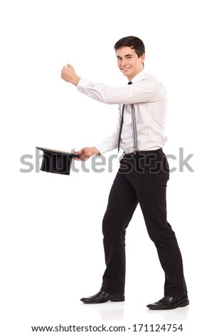 Happy young man pulling something out from top hat. Full length studio shot isolated on white. - stock photo