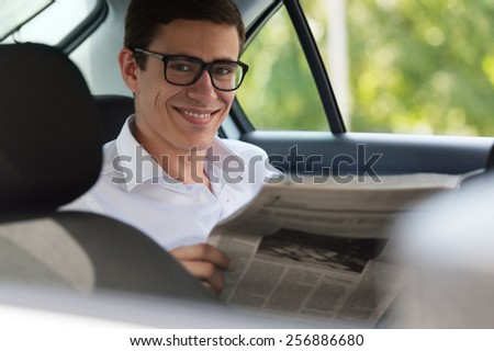Happy young man reading newspaper in car, smiling. - stock photo