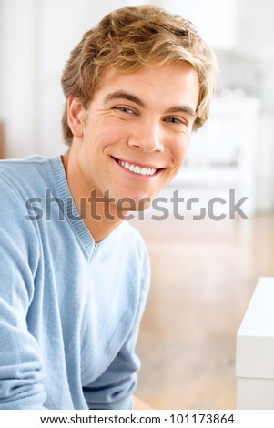 Happy young man relaxing at home looking at camera smiling - stock photo