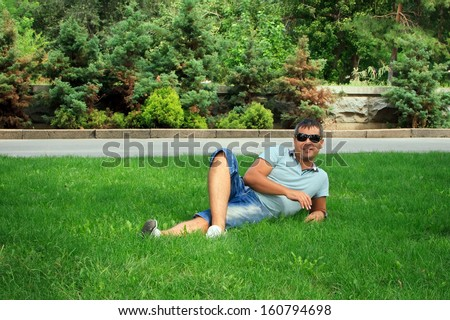 Happy young man relaxing on the green grass - stock photo