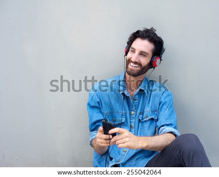Happy young man relaxing with mobile phone and headphones - stock photo