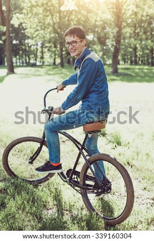 Happy young man riding a bicycle in a park and smiling. Attractive guy with glasses with a fashionable bicycle outdoors - stock photo