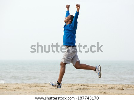 Happy young man running outdoors and celebrating with arms raised - stock photo