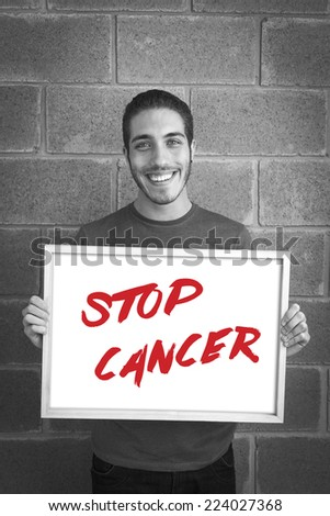 happy young man showing and displaying board with text: Stop Cancer Campaign
