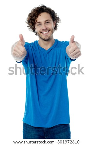 Happy young man showing thumbs up gesture - stock photo