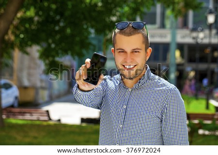 Happy young man shows a mobile phone screen in summer street - stock photo