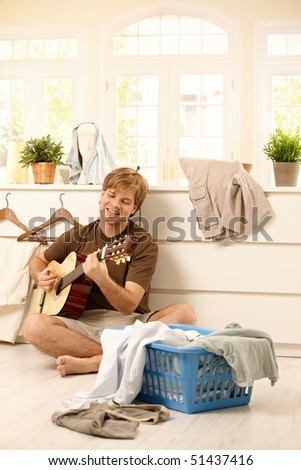Happy young man singing and playing guitar sitting on floor full of laundry instead of housework. - stock photo