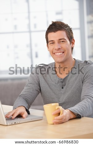 Happy young man sitting at table at home, smiling at camera, having tea, using laptop computer.? - stock photo