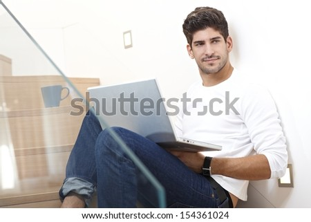 Happy young man sitting in stairway at home, using laptop computer, smiling, looking away. - stock photo
