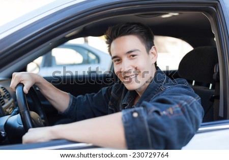 Happy young man sitting in the car - stock photo