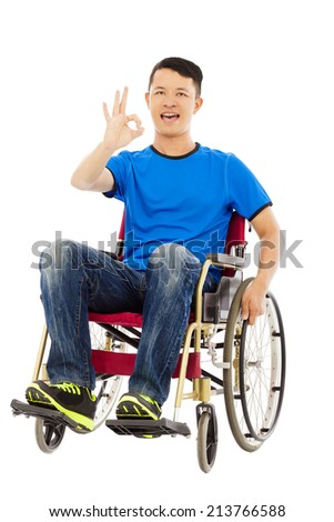 happy young man sitting on a wheelchair and ok gesture - stock photo