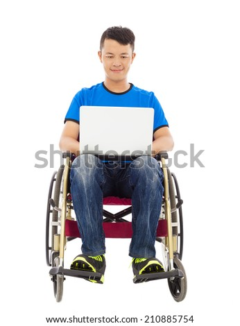 happy young man sitting on a wheelchair with a laptop - stock photo