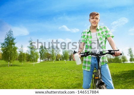 Happy young man sitting on the bike and holding water bottle riding in the park