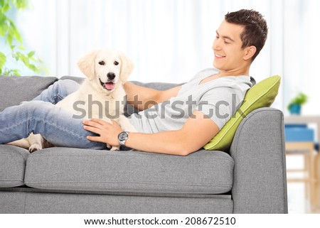 Happy young man sitting with his puppy on a sofa at home - stock photo