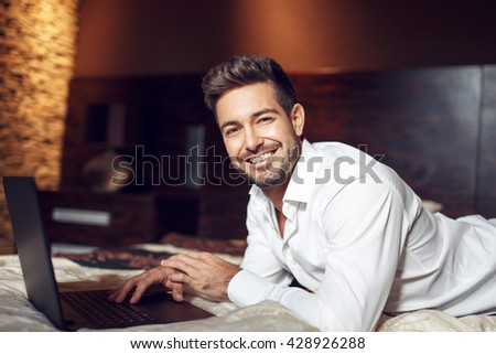 Happy young man smile with laptop in bed, online wireless communication from home - stock photo